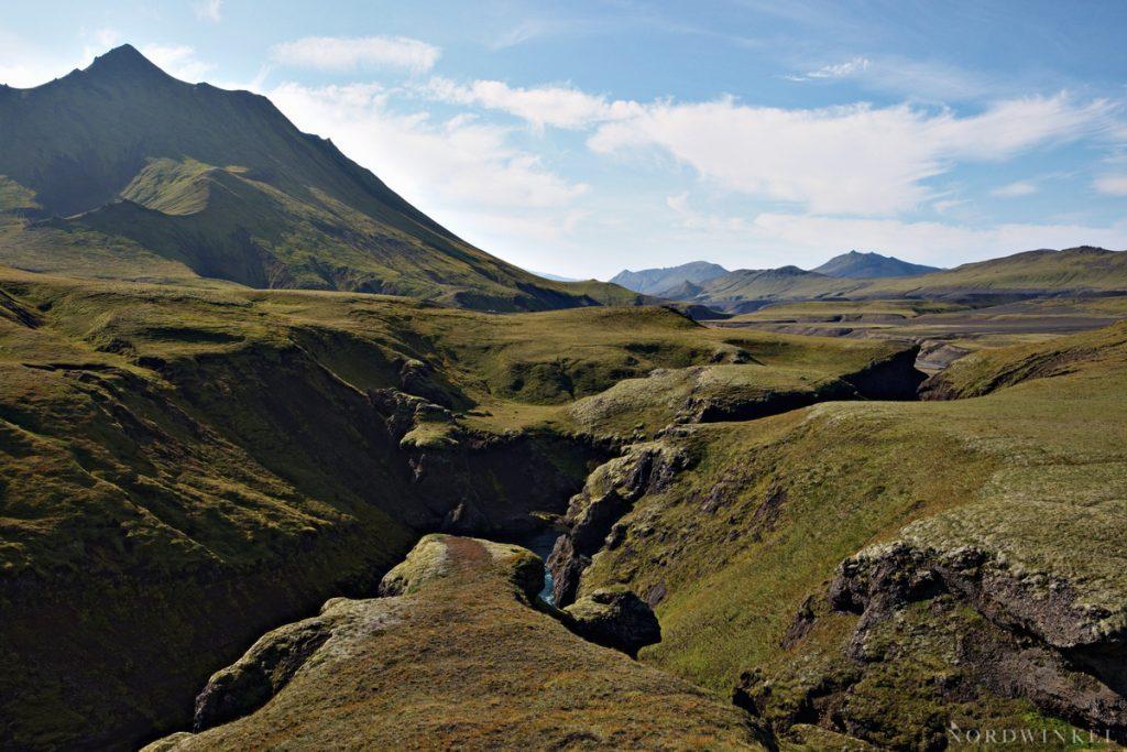 Blick auf grüne Landschaft und eine Schlucht