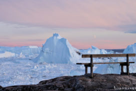 bench at the icefjord in Ilulissat with sunset and yellow and red sky