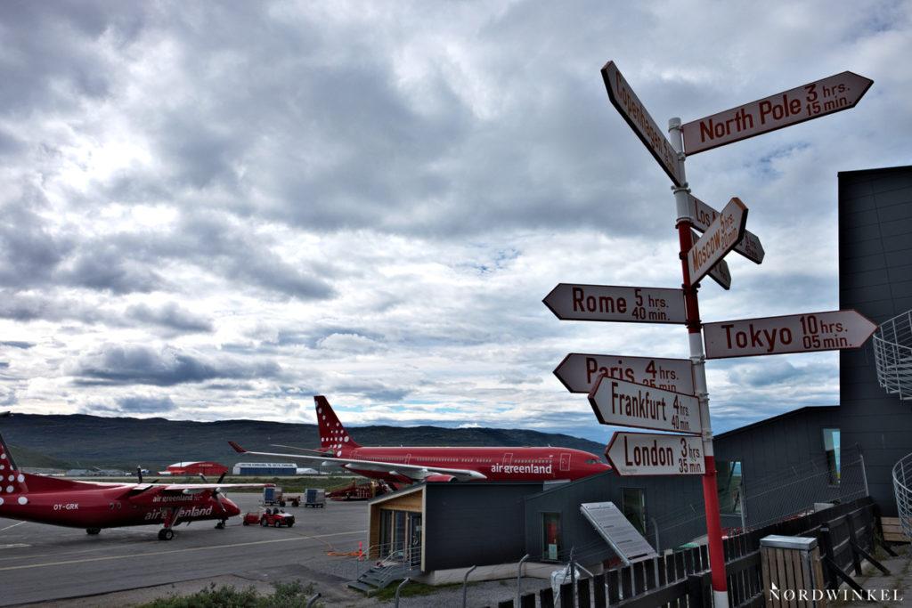 Wegweiser, der die Entfernung zu großen Metropolen und zum Nordpol angibt, gleichzeitig Startpunkt Arctic Circle Trail