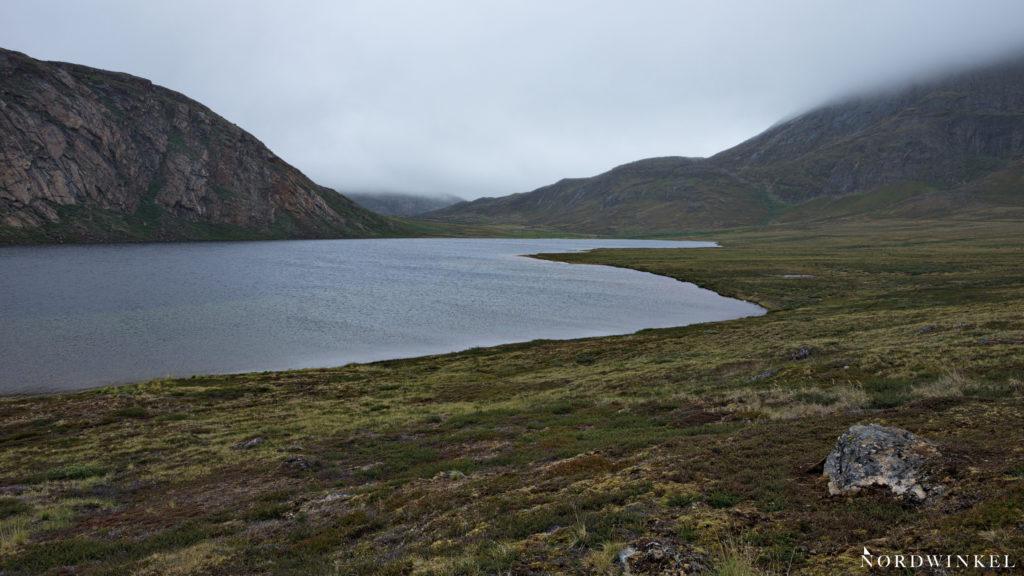 graues wetter tiefhägende wolken über einem see in grönland