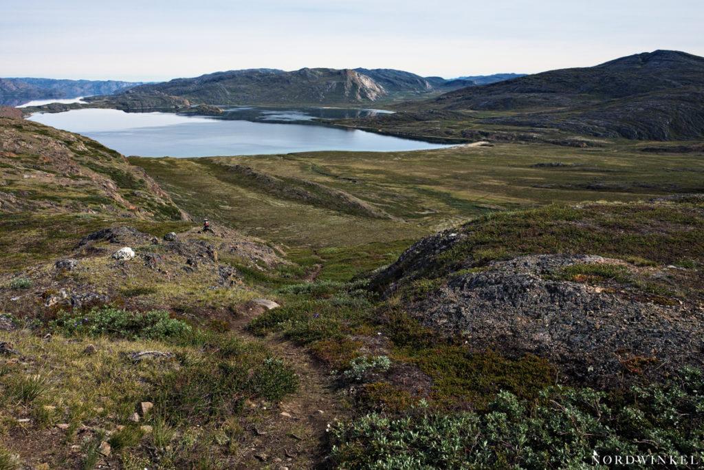 Blick auf den Tasersuaq mit Spiegelung der umliegenden Felswände und einem kleinen Sandstrand