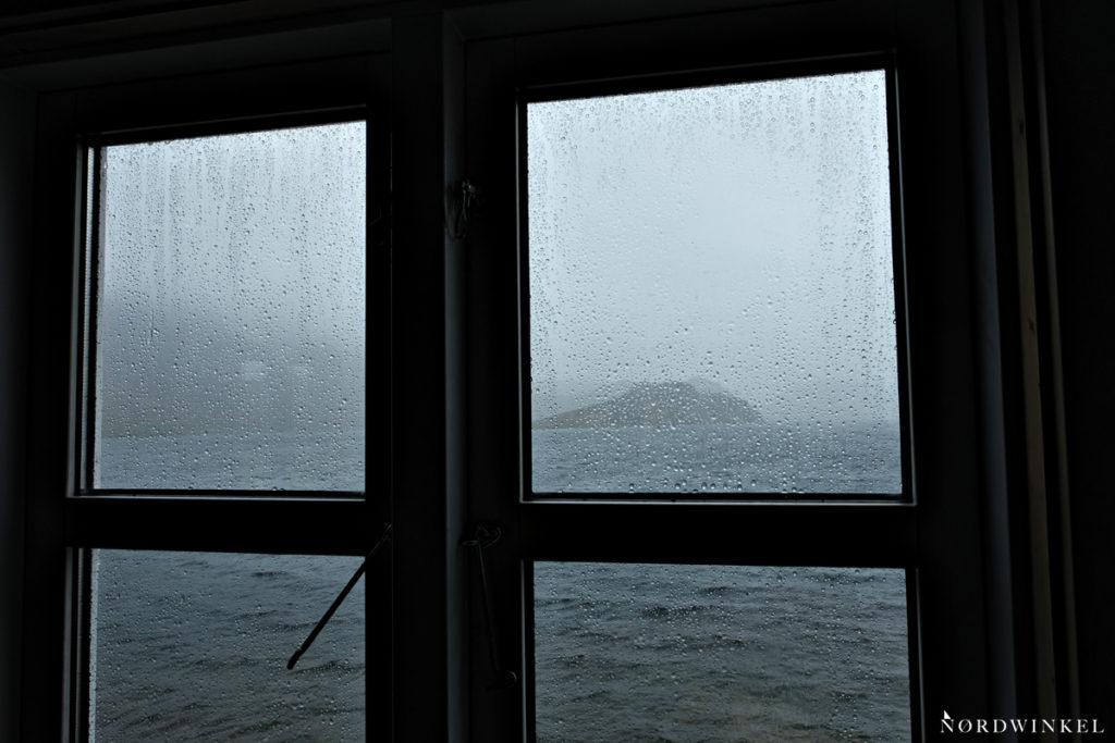 blick aus dem fenster der hütte auf den see der im regen verschwindet