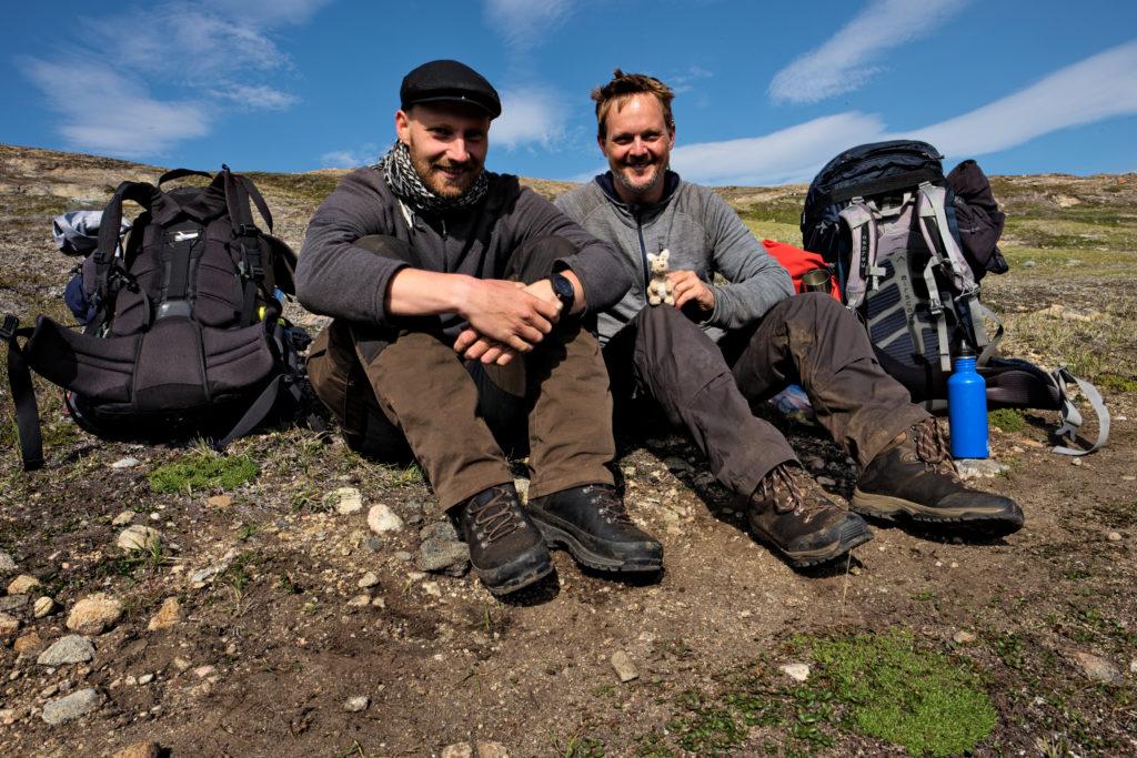 oleg und konrad sitzen in der grönländischen wildnis auf einem stein