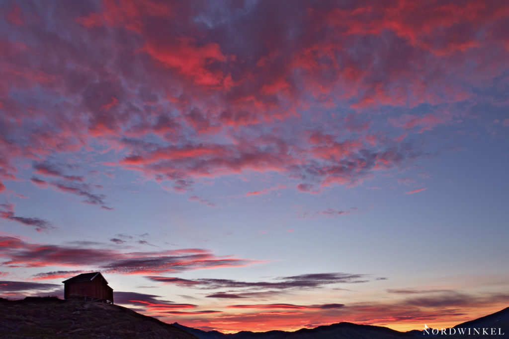 rot glühender himmel über einer hütte