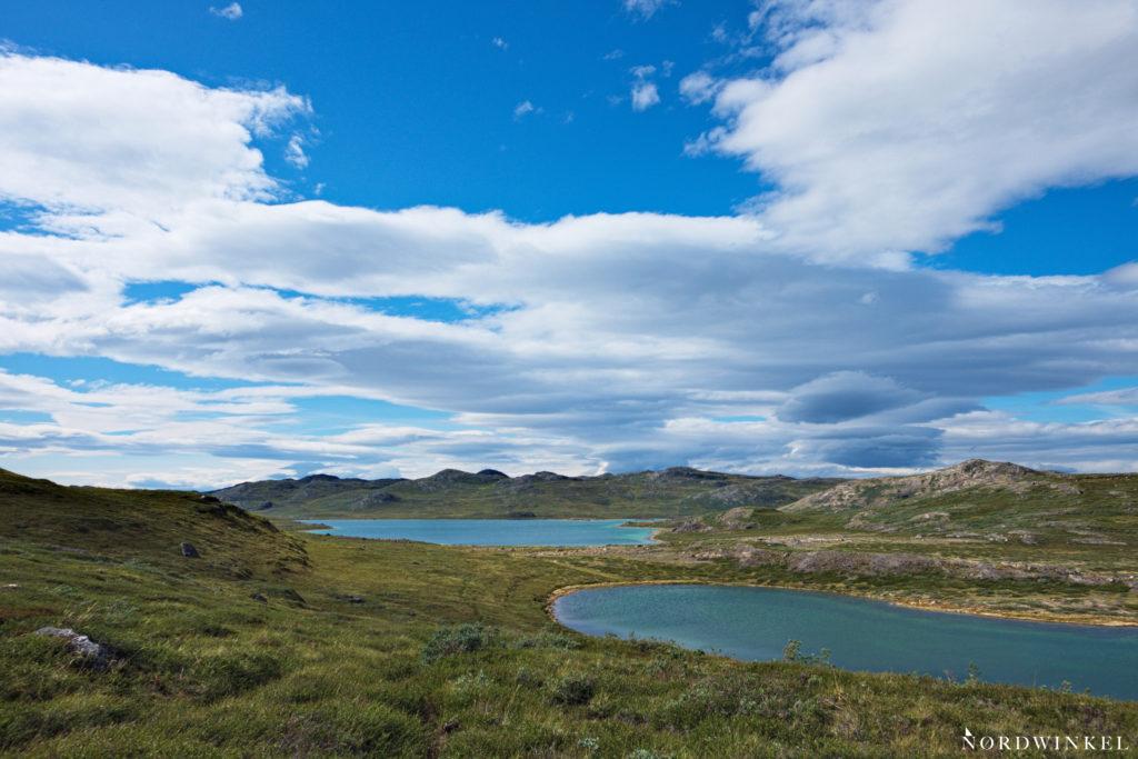 Blick über zwei blaue Seen unter blauem Himmel mit losen Wolken auf dem Arctic Circle Trail