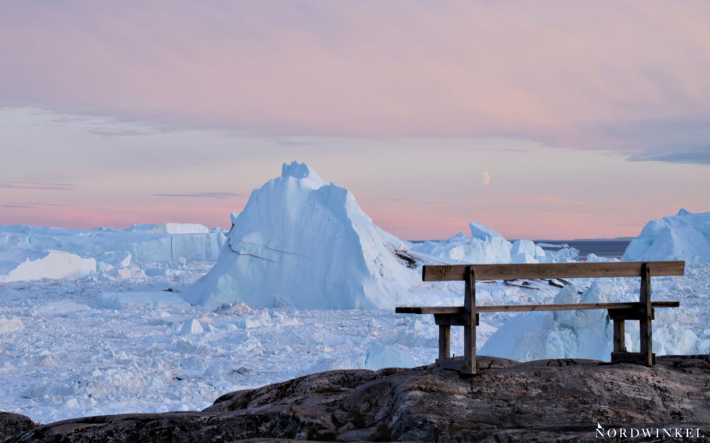 Bank über dem Eisfjord in Ilulissat zum Sonnenuntergang