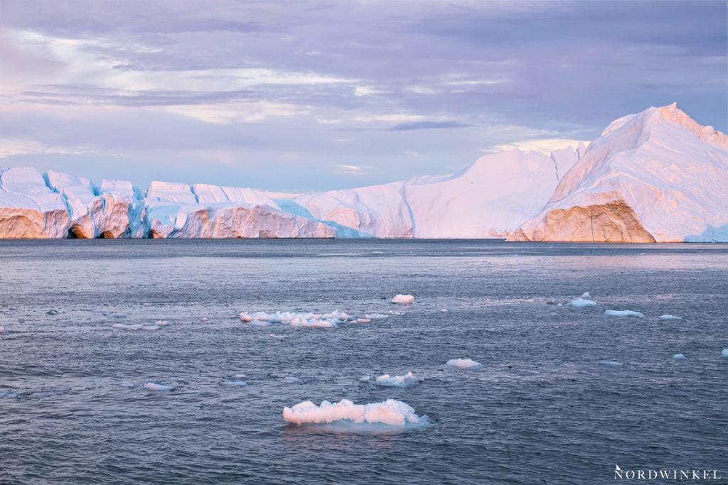 schwimmende eisberge im sonnenuntergangslicht
