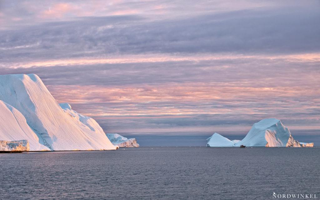boot zwischen schwimmenden eisbergen im licht der untergehenden sonne