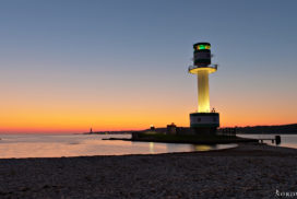 Ligthouse at the beach in front of a blue orange yellow sky because of sunrise