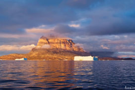 golden hour in uummannaq with icebergs an different enlightened layers of clouds