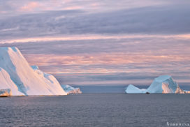 red sunset in the ice-Fjord in Ilulissat small boat in front of a huge block of ice