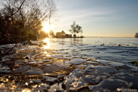 small pieces of ice on the surface of a lake with light of sunrise