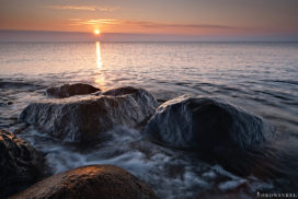 golden sunset at baltic sea with stones in foreground and splashing waves