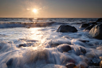 Sunrise over a stony beach with a lot of water splashing over the rocks