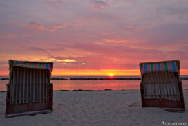 beach chairs at sunrise in the sand, baltic sea in the background and lightning sky with rising sun in shades of red and yellow