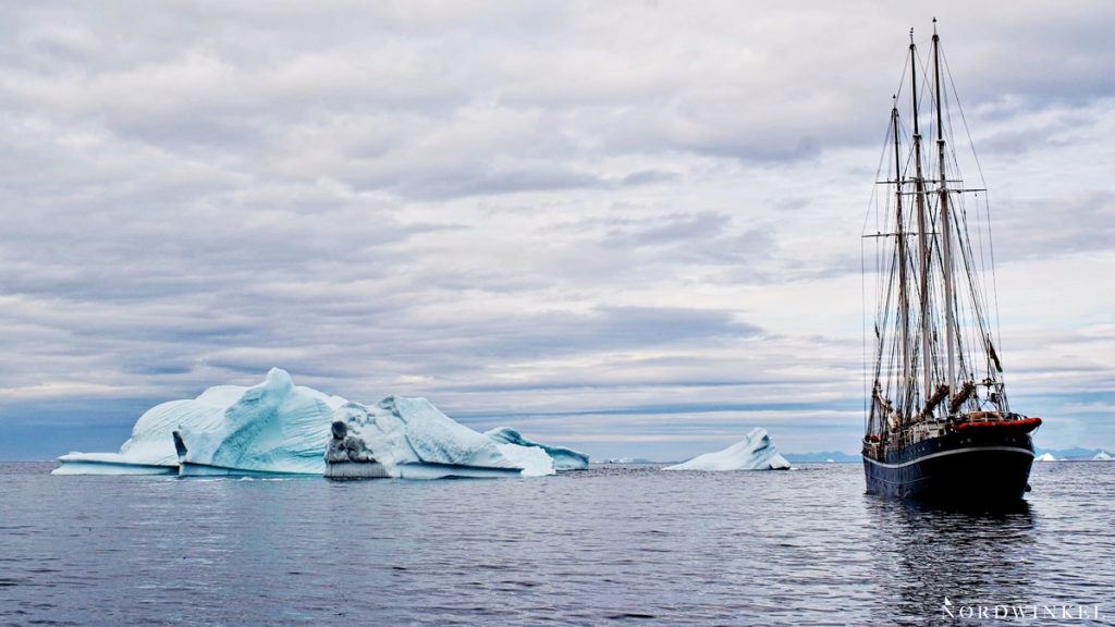 Segelschiff zwischen großen Eisbergen