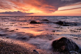 sunset in Dänisch-Nienhof with the baltic sea splashing over stones under a red lit eveneing sky