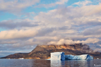 big iceberg in front of the uummannaqmountain covered by a low cloud layer of clouds at sunset inside uummannaqfjord