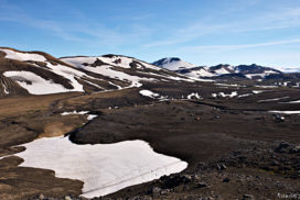 view over the plateau in hrafnntinusker with a blue sky over brown rocky ground and a couple of snowfields