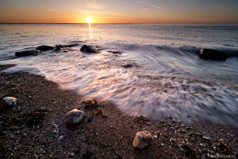 Baltic sea splashes over stones at the evening under a golden sun