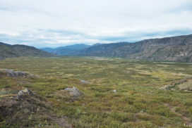 green land in Greenland under a cloudy sky but with a nice view over the next stage at the Arctic Circle Trail