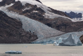 big icebergs inside a Fjord in Eastgreenland under a dark grey sky and a big glacierfront in the background
