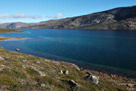 lake amitsorsuaq under blue sky with green-blue water at the arctic circle trail