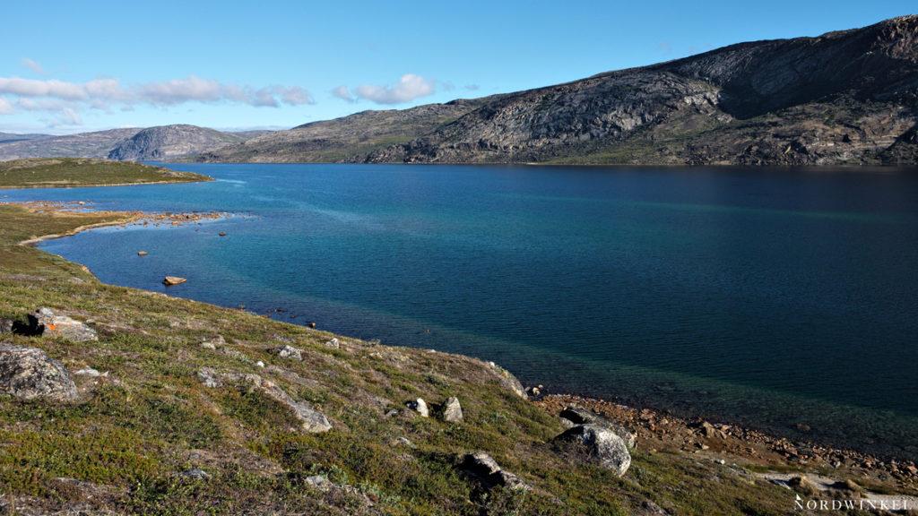 Blick auf dem Arctic Circle Trail vom grünen, felsigen Ufer auf den blauen See Amitsorsuaq