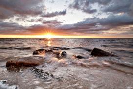 Sonnenuntergang an der Ostsee fotografieren Beispielbildmit Steinen, Ostsee, Wolken und leuchtender Sonne