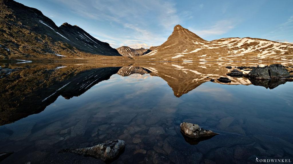 spiegelnder berg vor gebirgssee