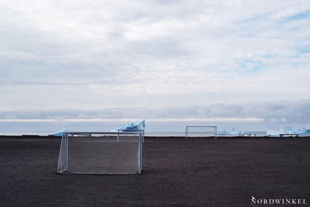 fussballfeld qeqertarsuaq vor eisbergen im meer