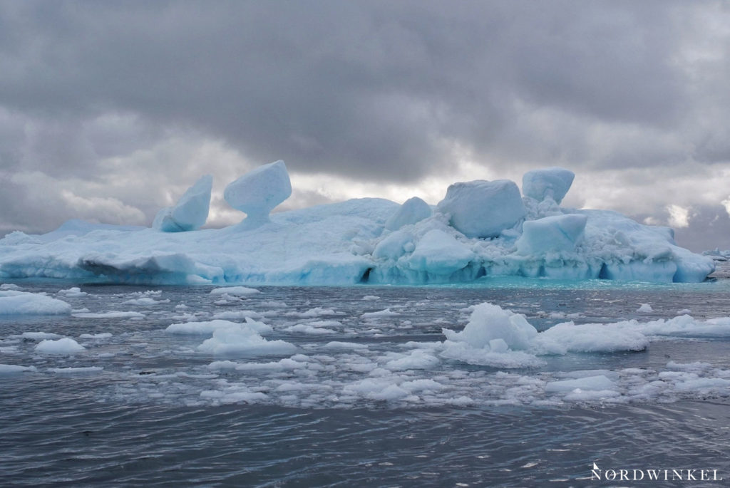 bizarr geformter türkiser eisberg mit losen eisbrocken an der oberfläche