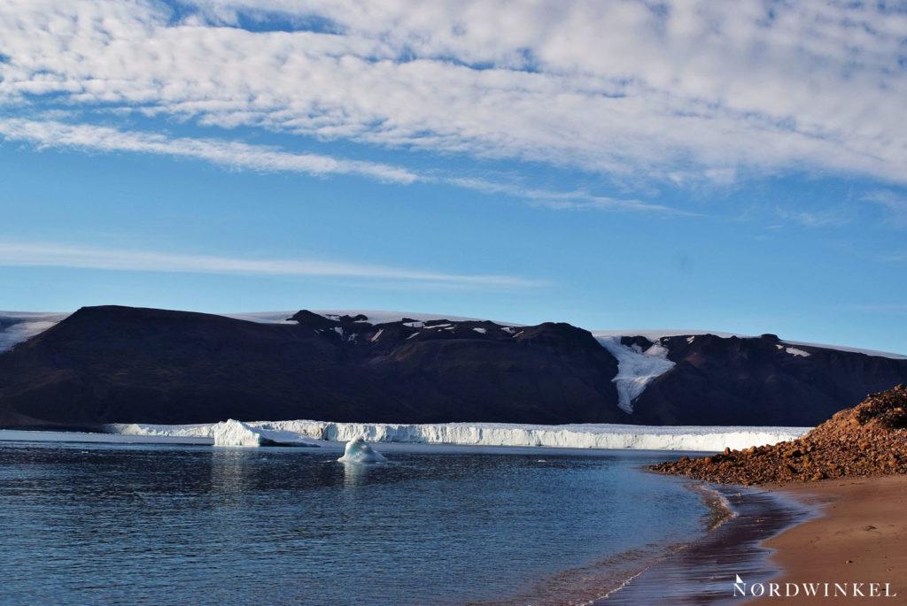 gletscherfront im moris-jesup-fjord mit einzelnen eisbrocken im wasser