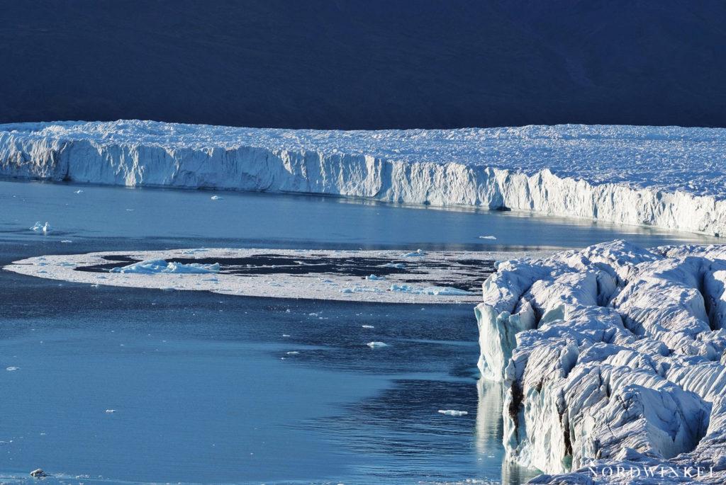 wellen breiten sich auf dem wasser aus als eis vom gletscher abbricht