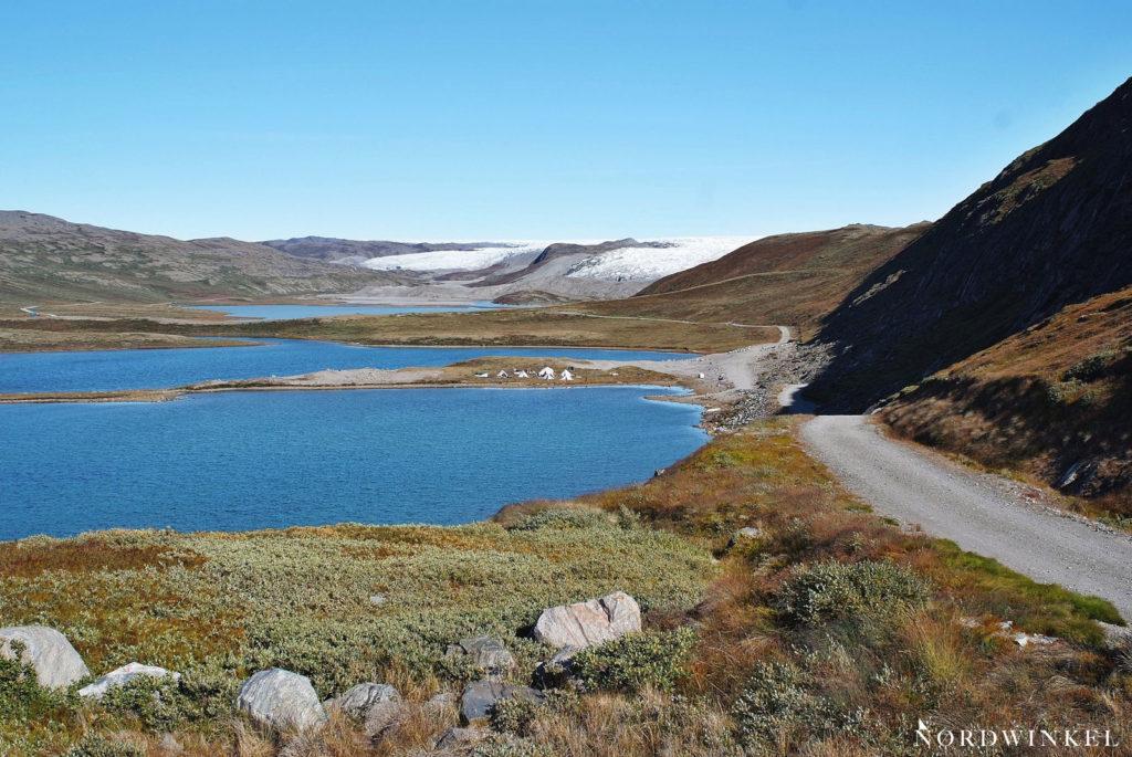 staubige schotterpiste in der grönländischen wildnis an zwei gletscherseen