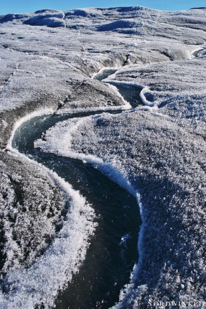 grüner schmelzwasserbach schlängelt sich durch eisbedeckte landschaft