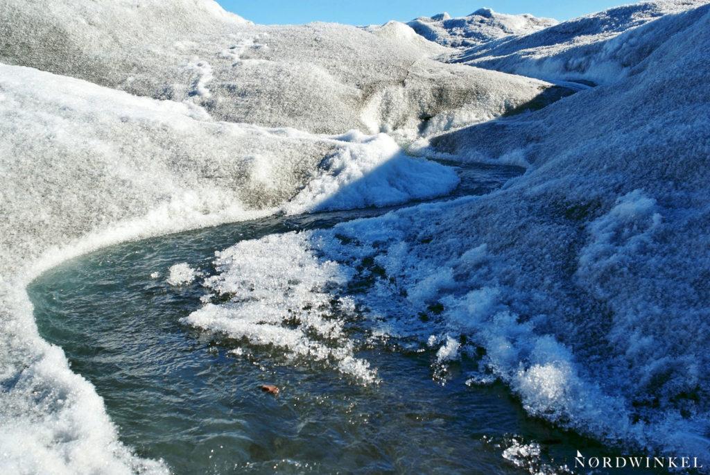 schmelzwasserfluss strömt durch eisbedeckte landschaft