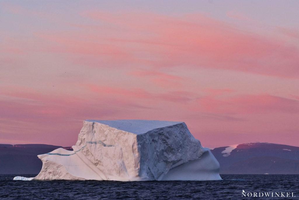 ein kirchturmhoher eisberg im abendrot