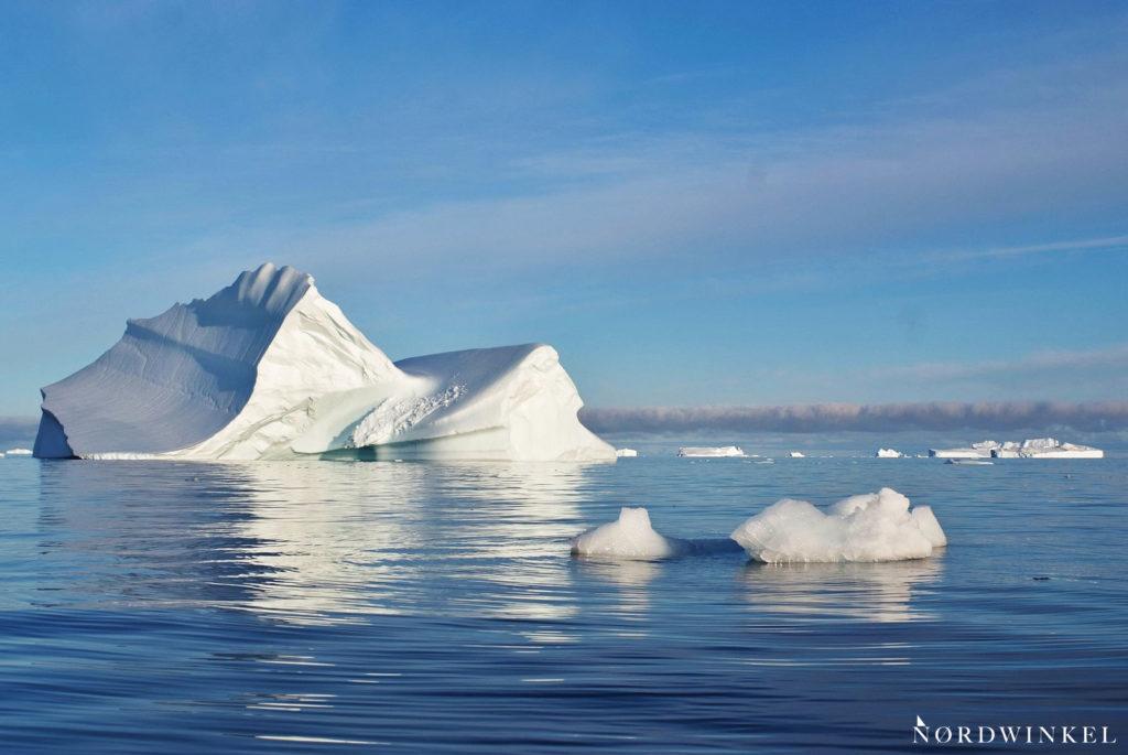 kleiner eisbrocken vor großem eisberg