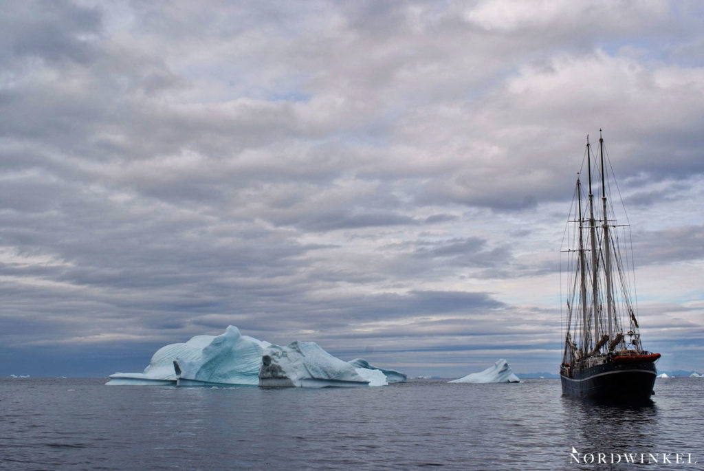 segelschiff zwischen blau leuchtenden eisbergen unter grauem himmel
