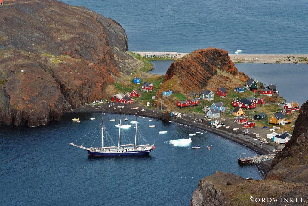 ankerndes segelschiff vor einer grönländischen siedlung
