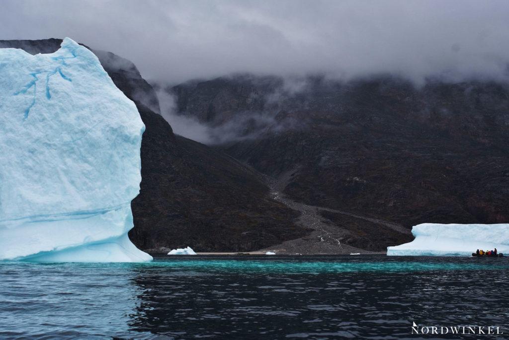 ein kleines schlauchboot weicht einem eisberg in der größe eines mehrfamilienhauses aus