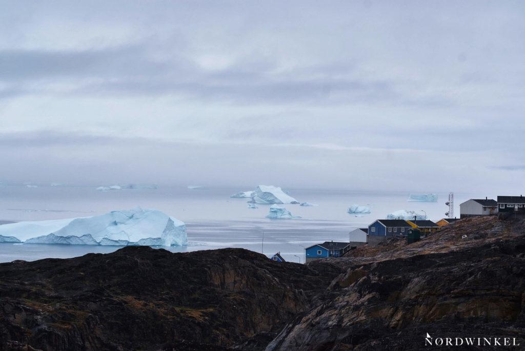 große eisberge im wasser vor der stadt uummannaq mit bunten häusern auf felsen