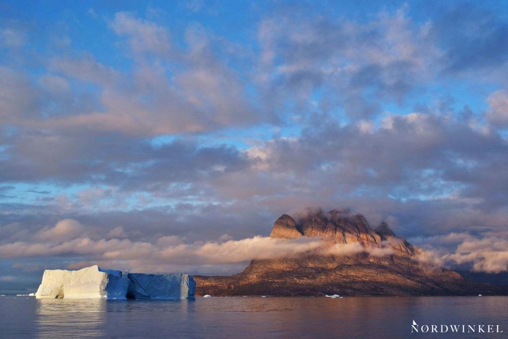 tiefhängende wolken vor uummannaq mit riesigem eisberg im meer