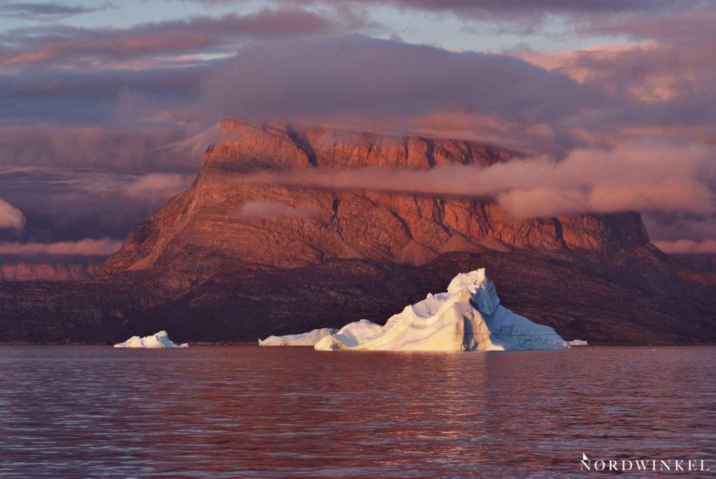 rotleuchtende wolken am uummannaqfelsen hinter einem eisberg