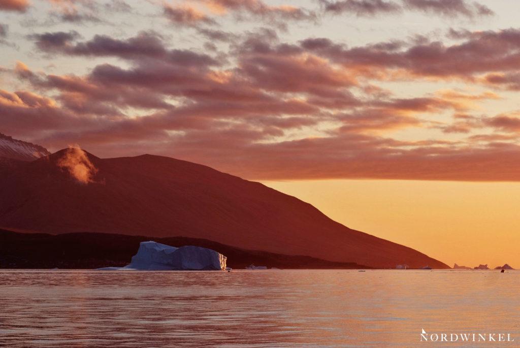 sonnenuntergangsstimmung im leuchtenden abendrot mit fels und eisberg