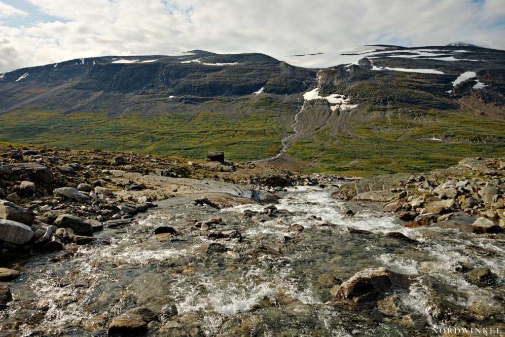 Flussquerung im Sarek mit Ausblick auf umliegende, schneebedeckte Berge