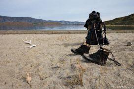 Trekking-Ausrüstung an einem Strand eines Sees
