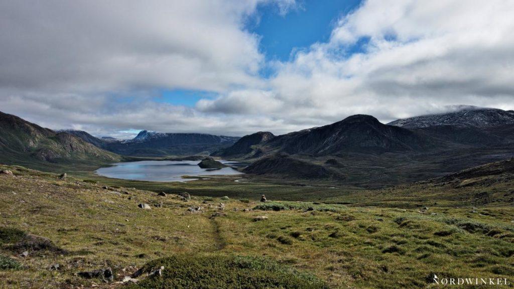 arktische Tundra unter bedecktem himmel mit einem see