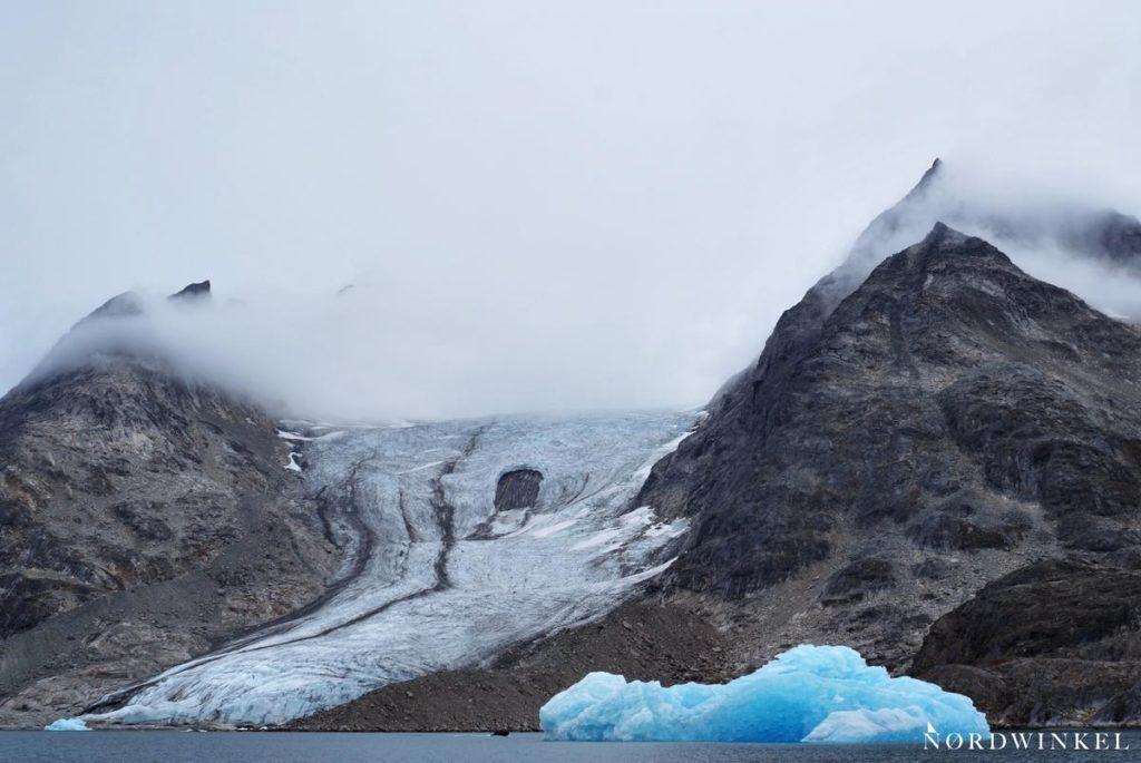 dicke wolken über rauhen bergen und einem gletscher an der küste mit einem blauen eisberg